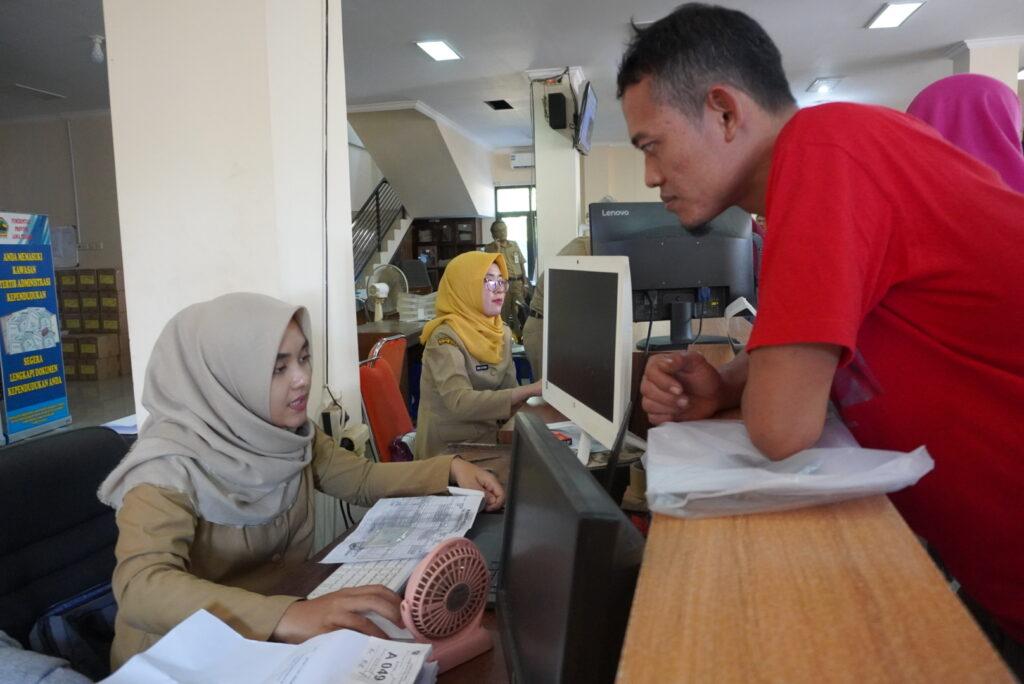 Petugas Disdukcapil Jepara sedang melayani masyarakat yang sedang mengurus adminduk.